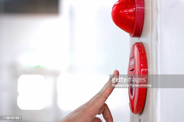 hand pulling fire alarm on the wall - sinal de emergência informação imagens e fotografias de stock
