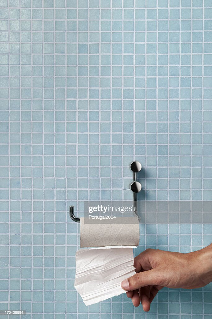 Hand pulling last square of toilet paper from the roll : Stock Photo