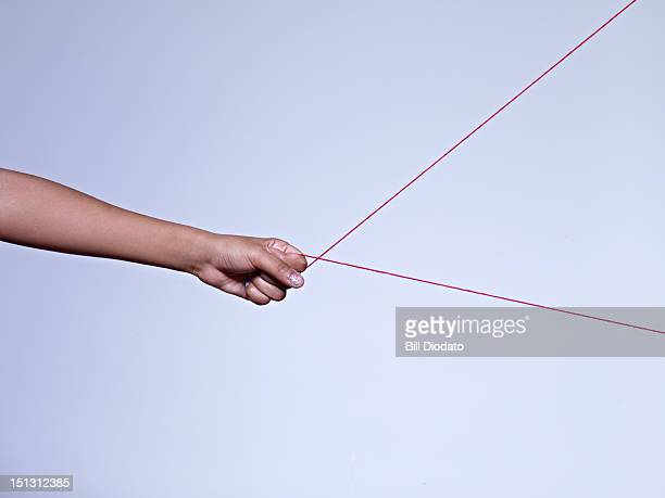 hand pulling on string