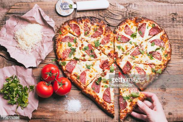 Hand pulling slice of heart-shaped pizza near ingredients on cutting board