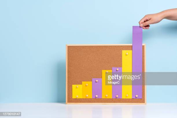 hand pulling up rising bar chart - improvement stock pictures, royalty-free photos & images