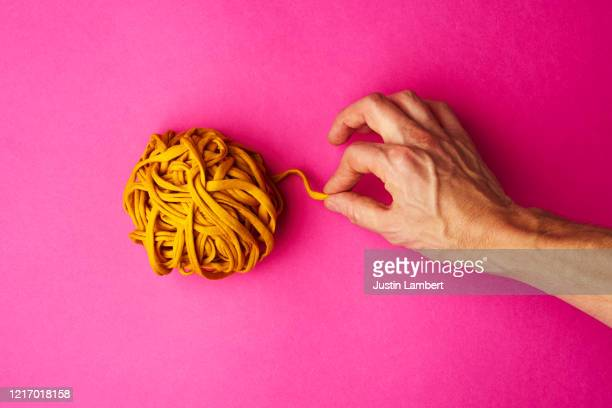 hand pulling yellow thread from a tightly wound ball - cerebrum stock pictures, royalty-free photos & images