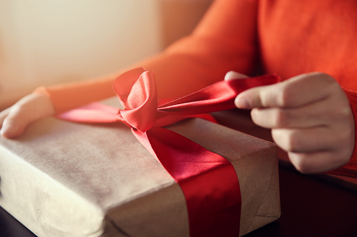 Hand pulls red ribbon on a gift wrapped in brown paper 893039466