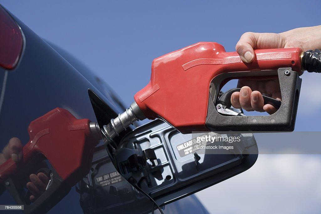 Hand pumping gas into automobile : Stockfoto