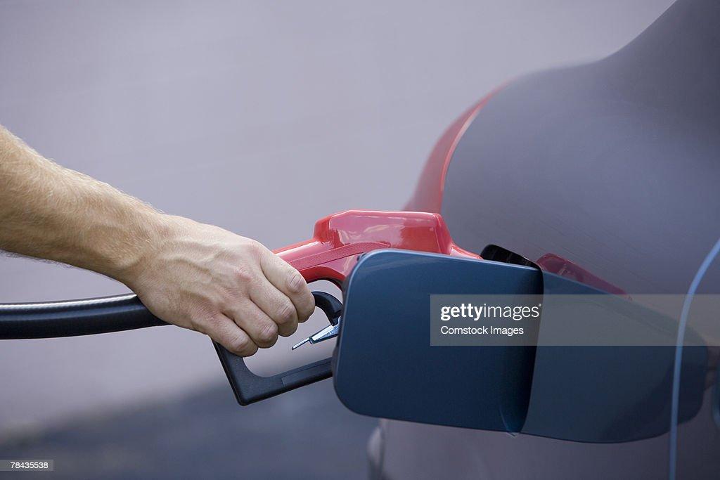 Hand pumping gas into vehicle : Stockfoto