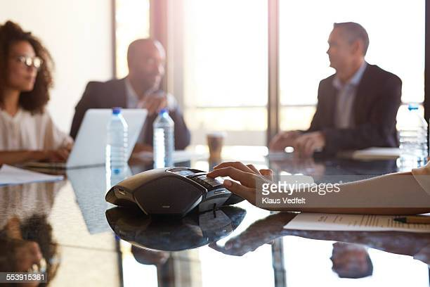 hand pushing digits on conference phone - conference call stock pictures, royalty-free photos & images