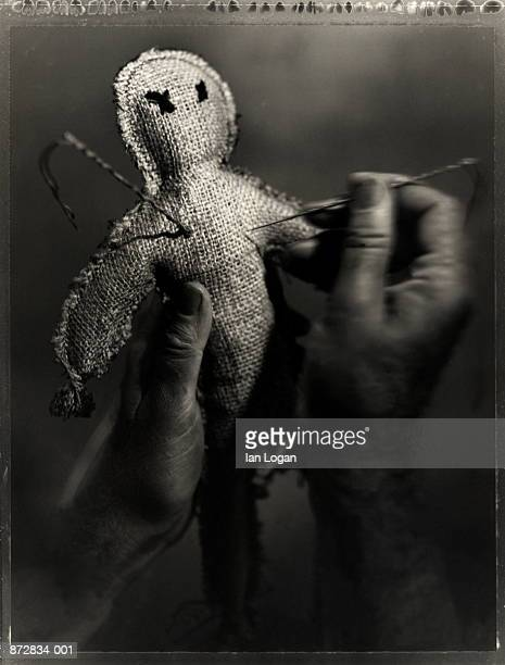 hand pushing pin into voodoo doll (b&w) - voodoo doll stock photos and pictures