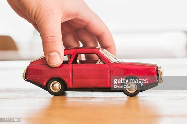 Hand pushing vintage red toy car