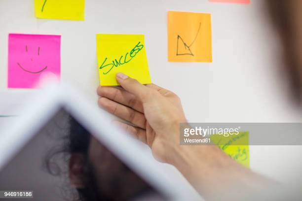 Hand putting a sticky note on board