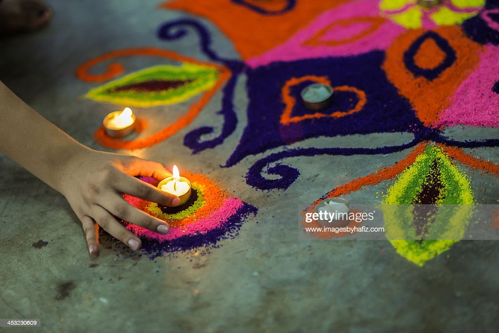 A hand putting an oil lamp on colorful rangoli : Stock Photo