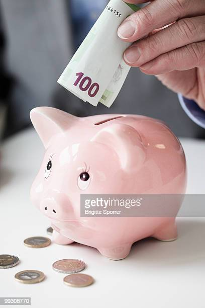 Hand putting banknote into piggy bank