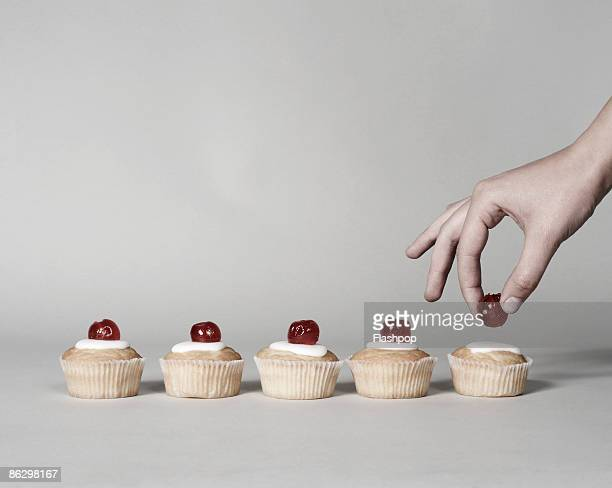 Hand putting cherry on a cake