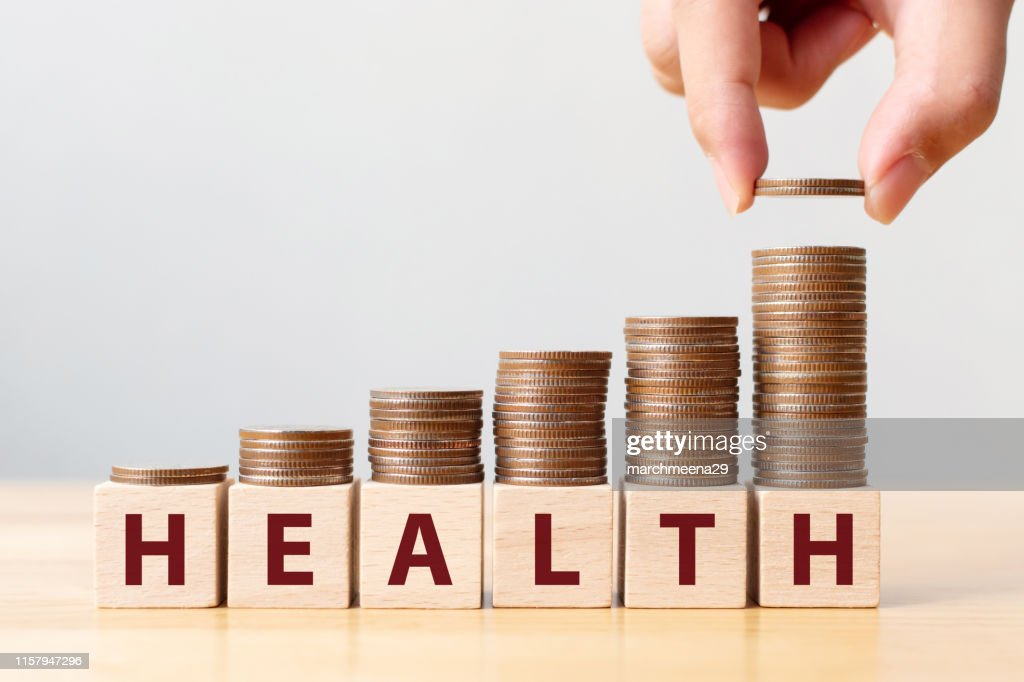 Hand putting coins on stack stair as step growing growth and wooden cube block with word HEALTH. Investment health and insurance fund concept : Stock Photo