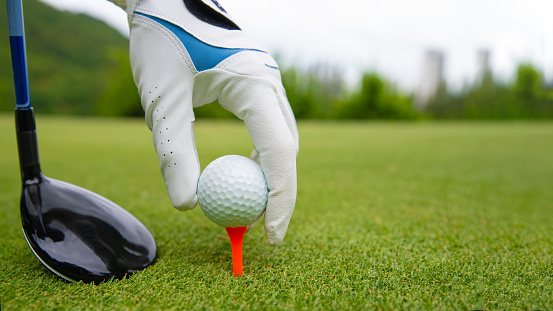 Hand putting golf ball on tee in golf course 1066999046