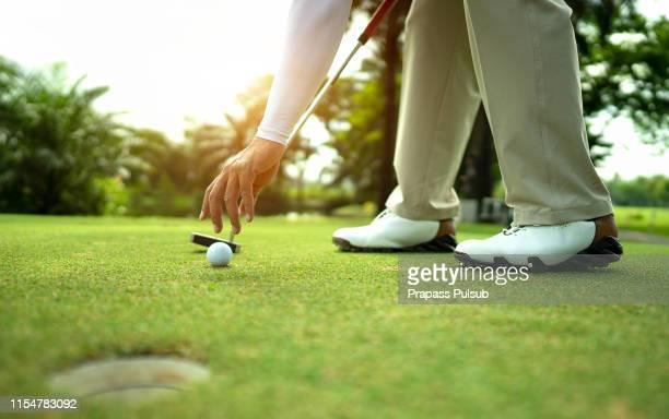 hand putting golf ball on tee in golf course - putting imagens e fotografias de stock