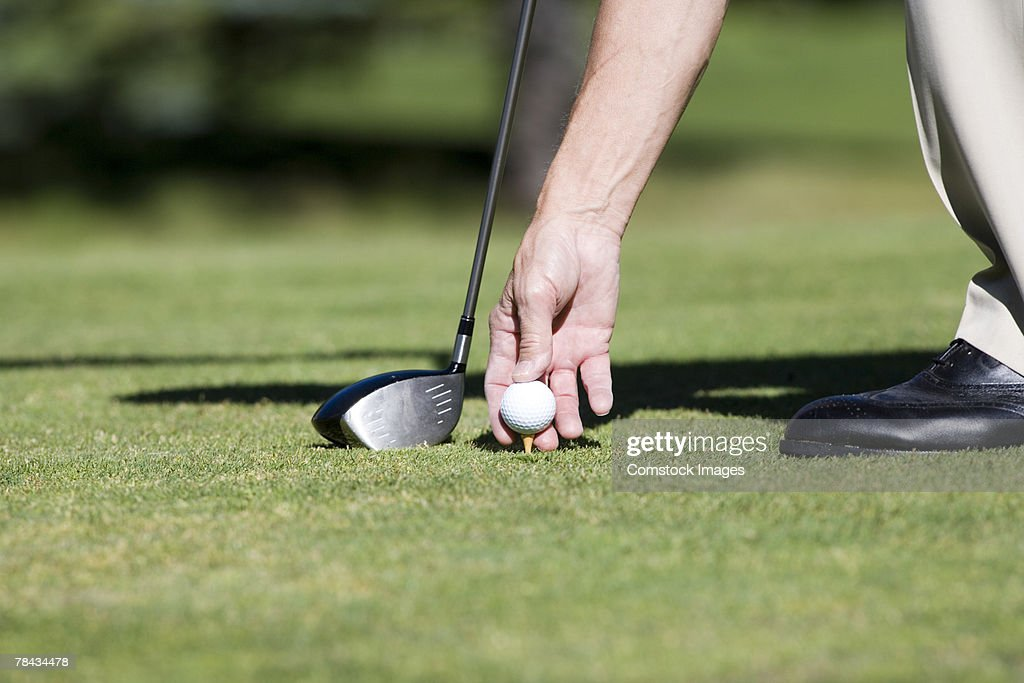 Hand putting golf ball on tee : Stockfoto
