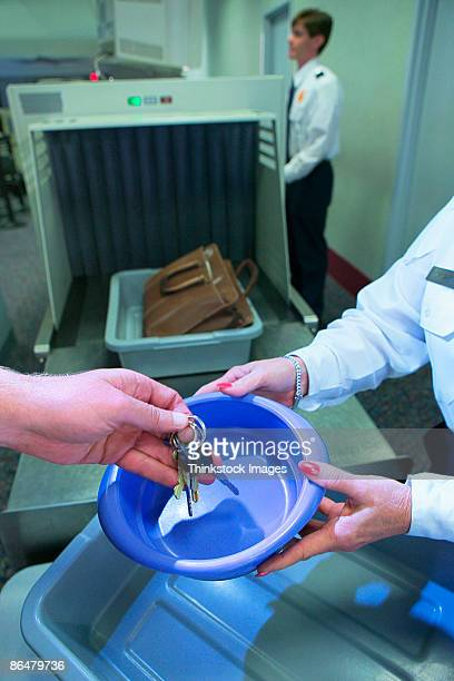 Hand putting keys in bucket at airport security checkpoint
