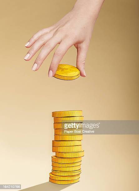 Hand putting paper gold coin on stack of coins