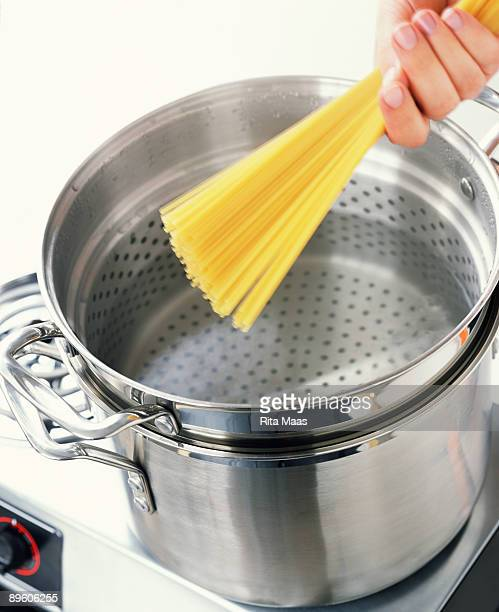 Hand putting pasta in pot