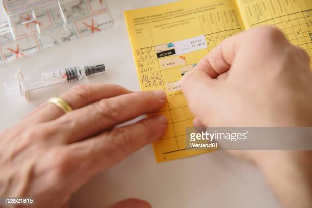 Hand putting sticker in vaccination pass