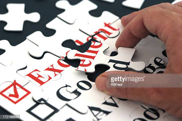 Hand putting together white puzzle pieces with red letters