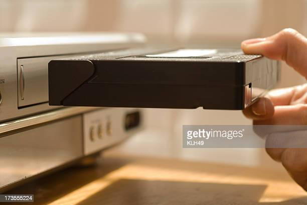 Hand putting VHS tape in a VCR