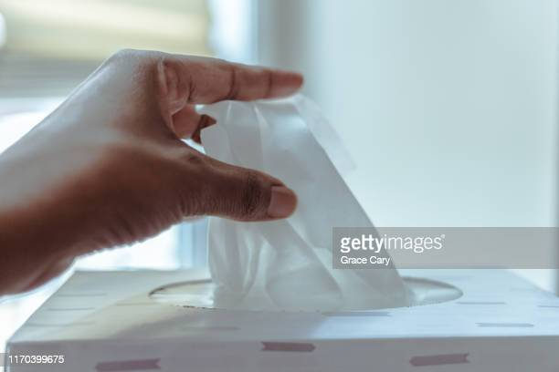 hand reaches for facial tissue - ティッシュ ストックフォトと画像