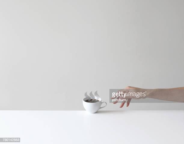 hand reaching for a conceptual cup of coffee - reaching stock pictures, royalty-free photos & images