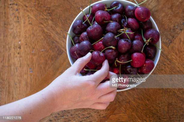 hand reaching for cherries. - ripe stock pictures, royalty-free photos & images