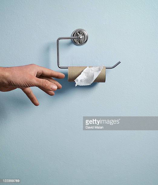 Hand reaching for empty toilet paper roll.