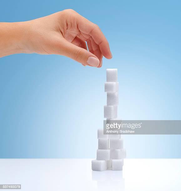 Hand reaching for sugar cubes