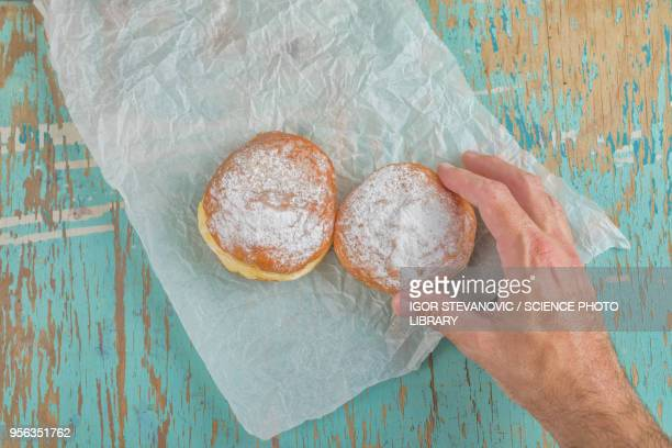 Hand reaching for sugary donut