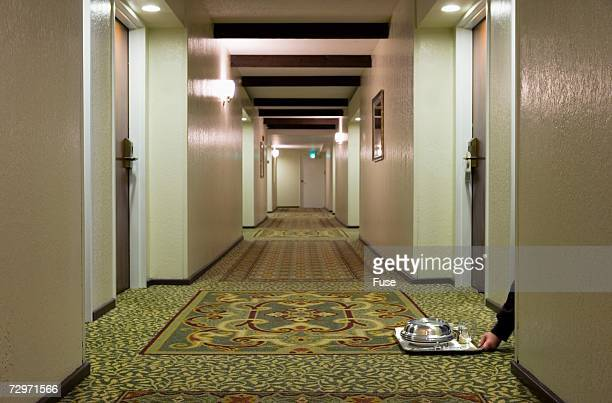 Hand reaching for tray in hotel corridor