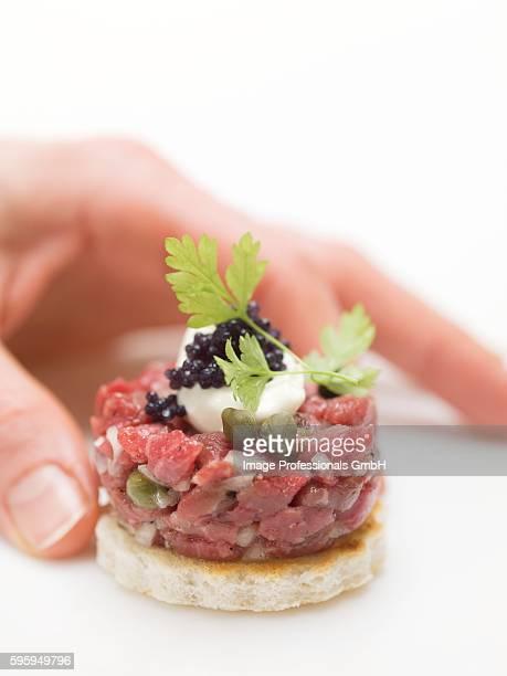 hand reaching for tuna tartare canap?? - canap�� photos et images de collection