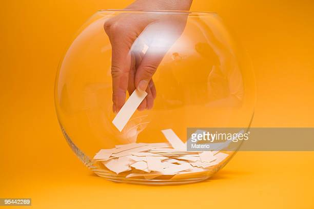hand reaching into a bowl to pick a lottery ticket - lucky draw stock photos and pictures