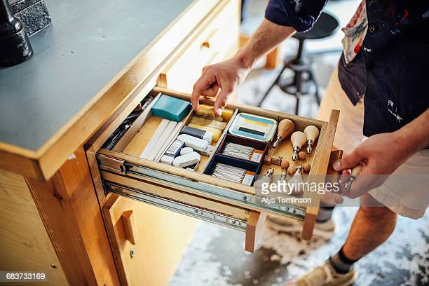 hand reaching into open drawer containing equipment and materials in book arts workshop - drawer stock pictures, royalty-free photos & images
