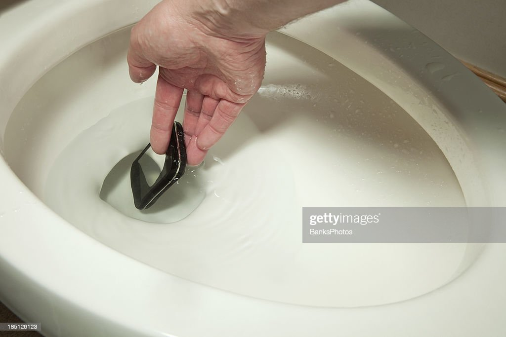 Hand Reaching Into Toilet To Retrieve A Mobile Phone Stock Photo ...