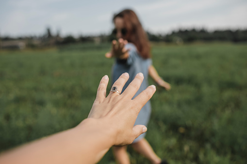 Hand reaching out for woman on a field - gettyimageskorea