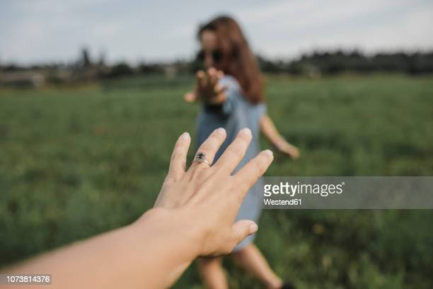 hand reaching out for woman on a field - reaching stock pictures, royalty-free photos & images