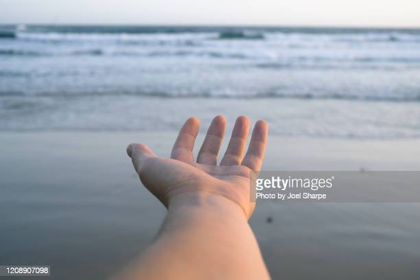 hand reaching out towards horizon - desire stock pictures, royalty-free photos & images