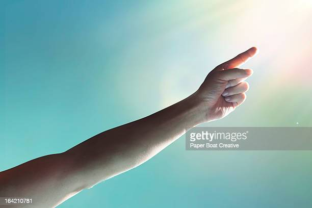 hand reaching to the sky and touching light