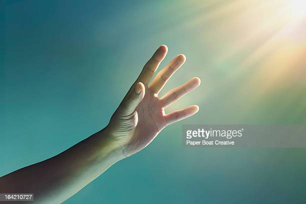 hand reaching towards glowing light from corner - religion stock-fotos und bilder