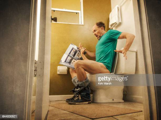 Hand reaching up for Caucasian man on toilet