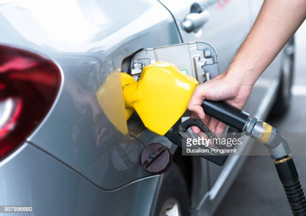 hand refilling the car with fuel, close-up. - gas tank stock photos and pictures
