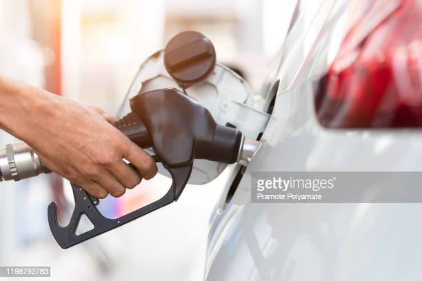 hand refilling the car with fuel, close-up, pumping equipment gas at gas station. - gasoline stock pictures, royalty-free photos & images