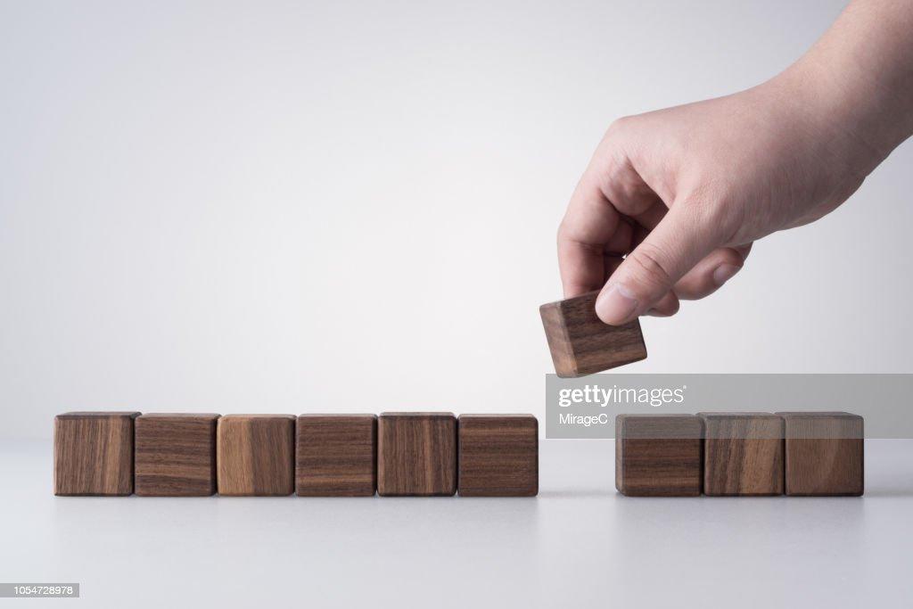 Hand Removing a Wood Blocks : Stock Photo