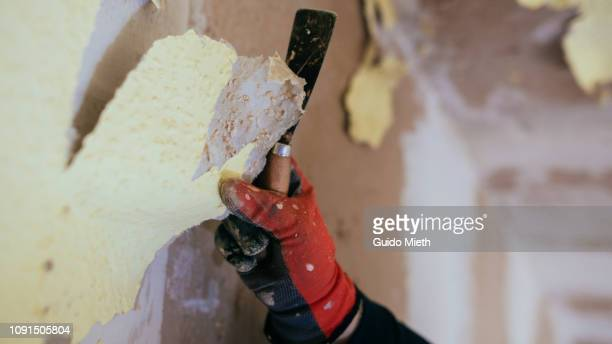 Hand removing old wall paper.