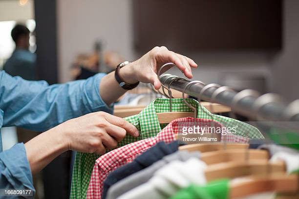 A hand removing or placing clothing on a rack