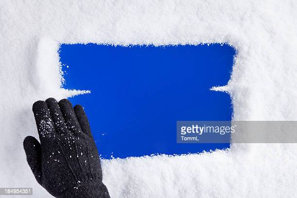 Hand Removing Snow From Window