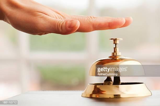 Mano tocando la campana en escritorio junto a la ventana